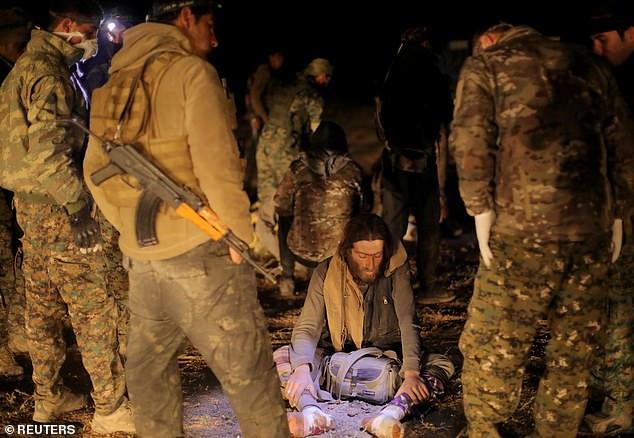 Боевики Сирийских Демократических сил (СДС) стоят рядом с человеком, эвакуированным из боевых действий в районе Багхауз.