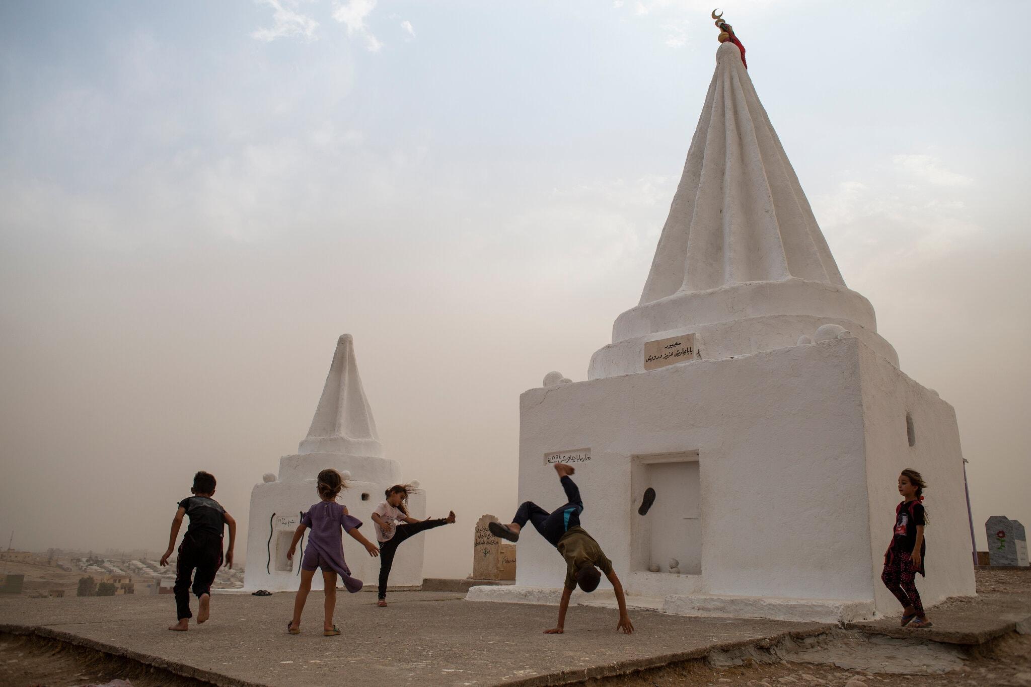 Дети езидов играют в августе под дождем. Храм в Курдистане на севере Ирака, деревня Ханке. Фото Хауре Халид для газеты «The New York Times»