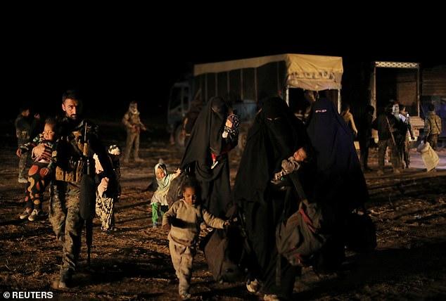 Недалеко от деревни Багхуз, провинция Дейр-эз-Зор, в Сирии. Вчера. Женщины, идущие с вещами и их детьми и бойцы SDF, помогающие им.