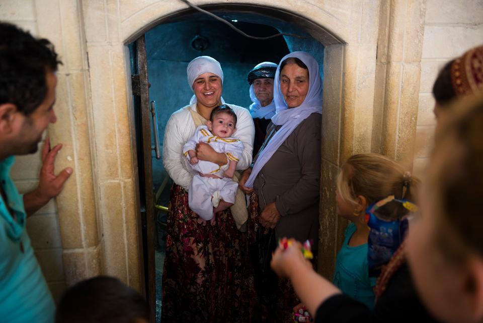 Лалиш, Ирак - 28 мая 2017: Семья езидов проводит обряд посвящения младенца в Езидизм в Священном Лалише, Ирак. Езиды - это курдское религиозное меньшинство, коренное население северной Месопотамии. GETTY